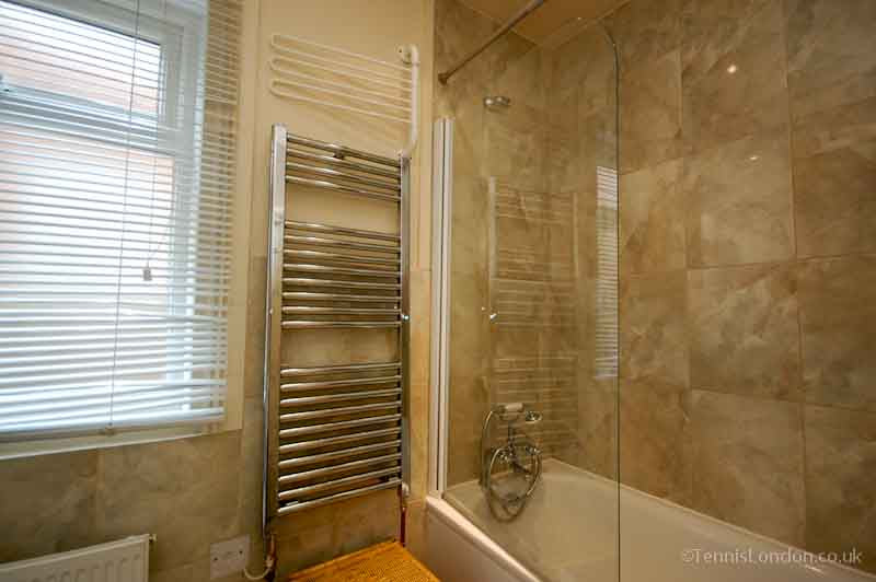 Natural mottled pattern bathroom tiles, with towel radiator and glass shower screen on a white bathtub