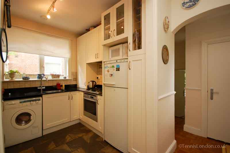 A poorly lit small white and cream kitchen
