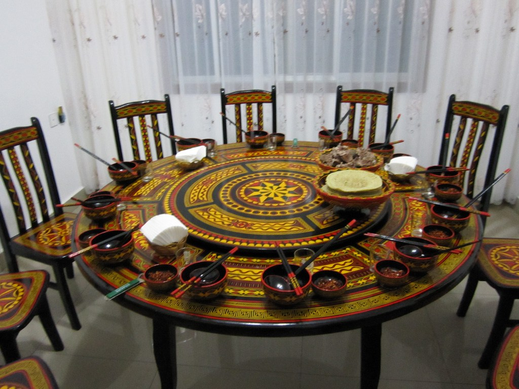 Black, yellow and red circle patterned round dining table with matching wooden chairs and bowls and chopsticks on the table