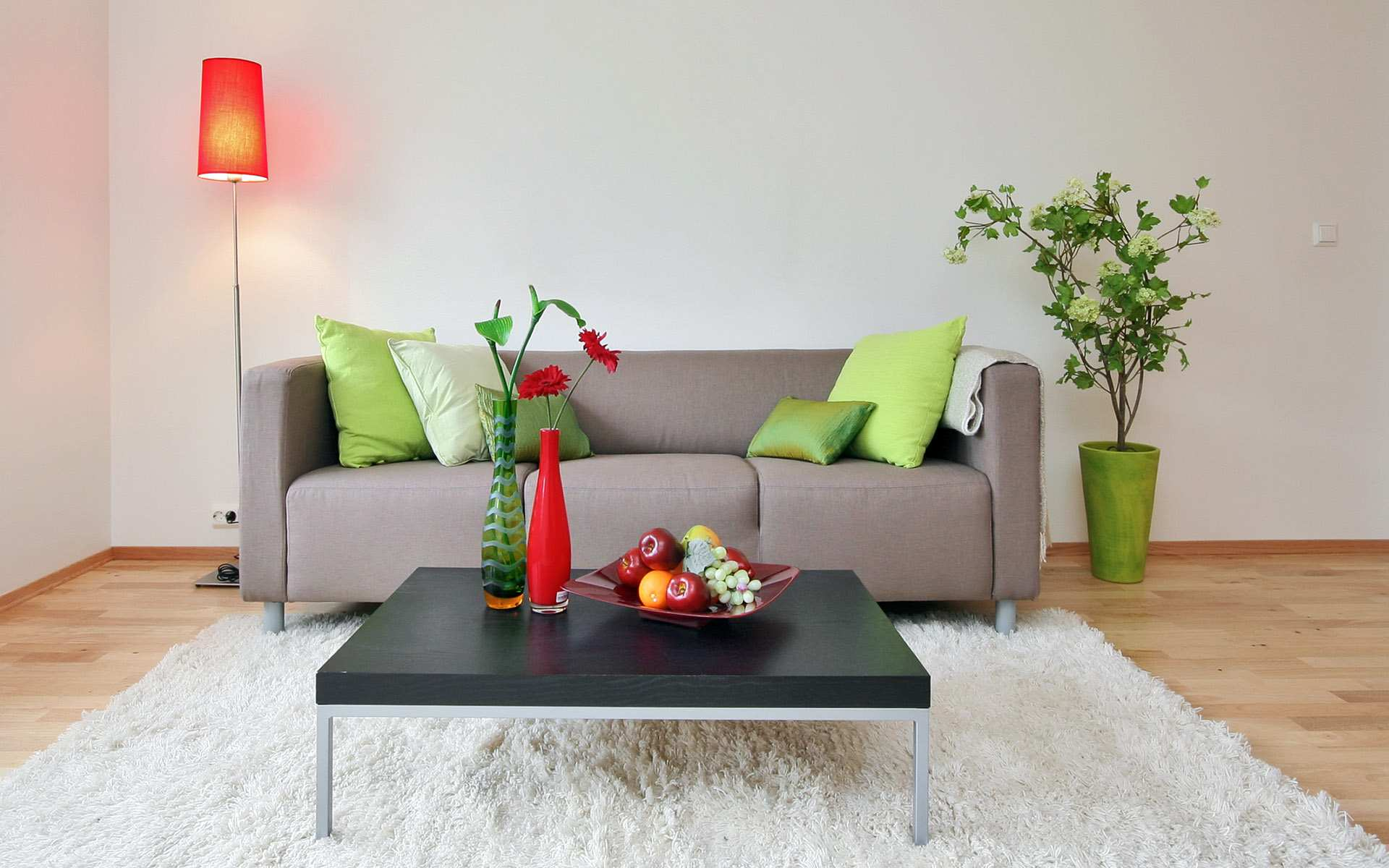 Beige Sofa On White Rug, Surrounded By Green And Red Accessories