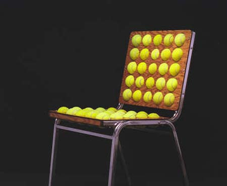 A wooden chair with metal frame, covered in tennis balls