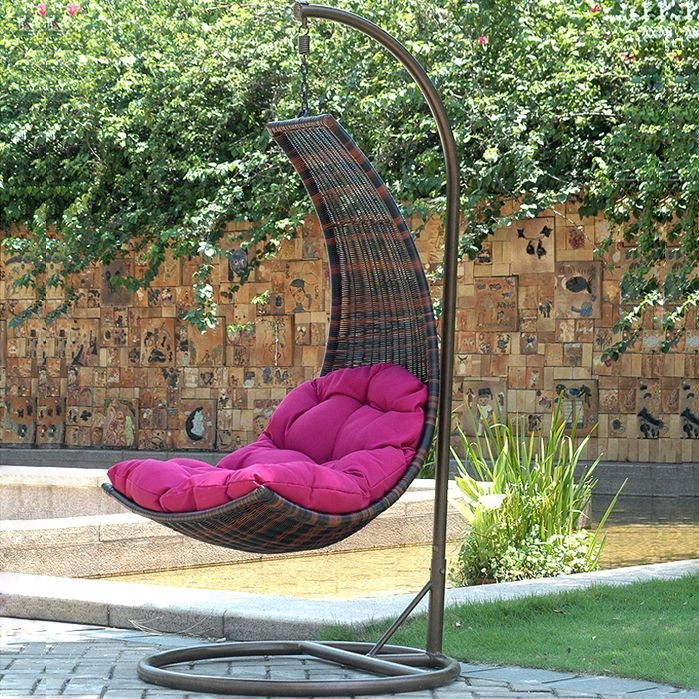 Curved Suspended Chair With Pink Cushion In The Garden