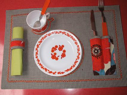 A picnic place setting with red and white bowl and cup on a roll out fabric setting