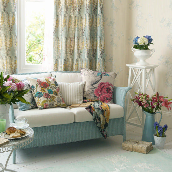 Cream living room with touches of duck egg blue, and matching wicker sofa and cream seat pads