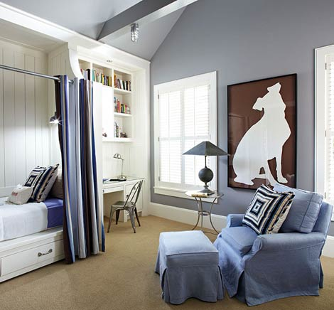 Grey bedroom with white shelves, desk and bed, plus blue armchair
