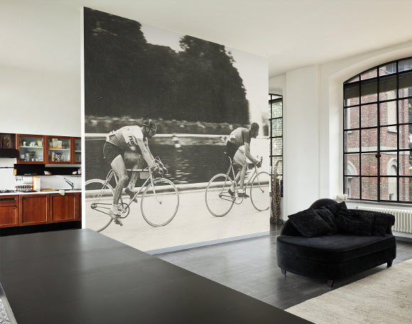 Wall to ceiling black and white canvas of two people cycling