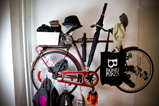 A bike mounted to a wall used to hang coats, hats and umbrellas on