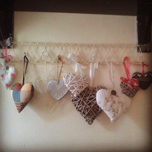 Heart shapes made from different materials hung from a metal heart design hooked rack