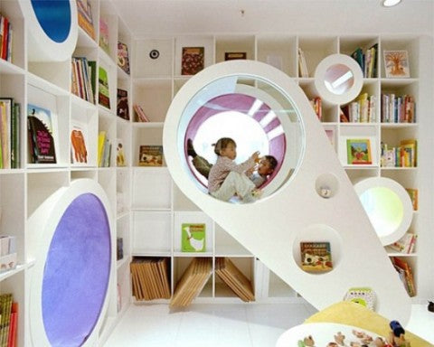 Funky kids bedroom with square white shelves floorto ceiling and futurist pods for sitting in and reading