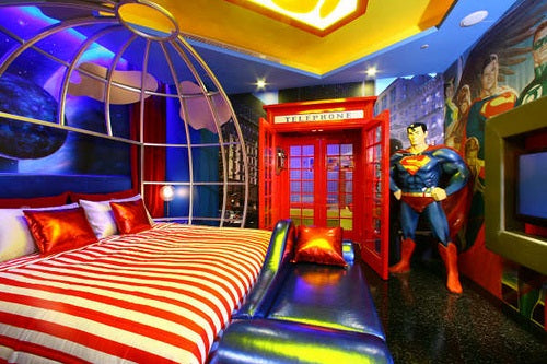 DC Comics style bedroom with wall art, bright lights and a life size Superman figure