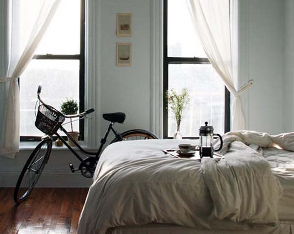 Bicycle leaning against a wall between two windows in a bedroom