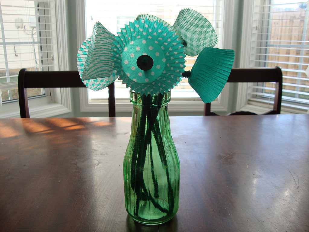 Green glass bottle with black pipe cleaners and cupcake cases used to make pretend flowers