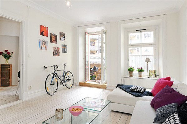 White living room with white corner sofa, plus bicycle leaning against a wall next to an open balcony door