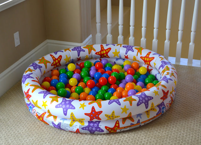 Inflatable paddling pool filled with ball pit balls