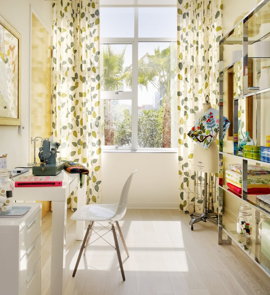 Modern and fresh sewing room with dark grey sewing machine on a white desk and a large bright window with floral cream and green curtains hung at the window