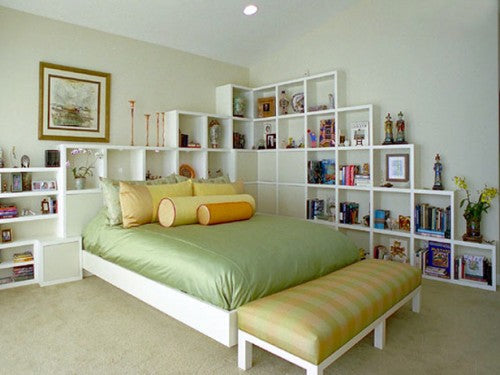 Light green bedroom and green bedding, with white square compartment shelves covering two walls of the room