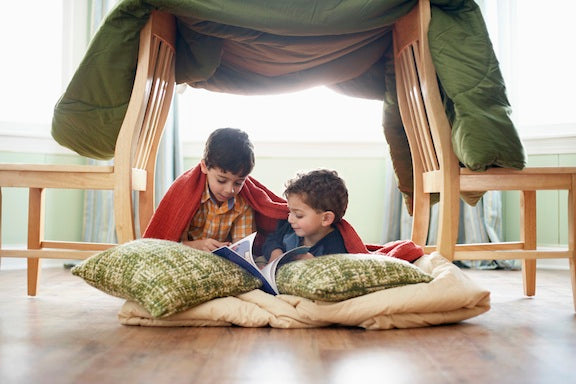 A blanket draped over two chairs to create a kids den tent, with two kids reading underneath
