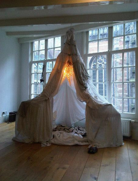 Kids play tent and fairy lights with the roof held up by a rope attached to ceiling beam