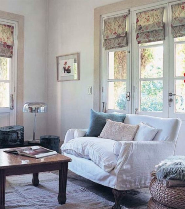 White and beige living room with small white arm chair and wooden coffee table, plus small beige roman blinds hung over individual window panes
