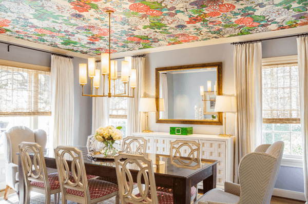 Light grey dining room with cream and gold accessories, wooden table with glass top and floral colourful wallpaper on the ceiling