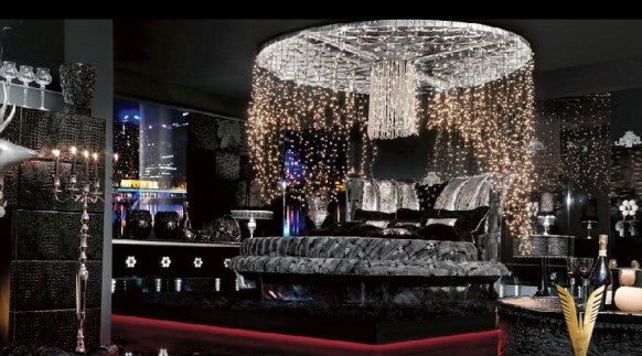 A black penthouse style bedroom with elegant fairy lights hanging from the ceiling