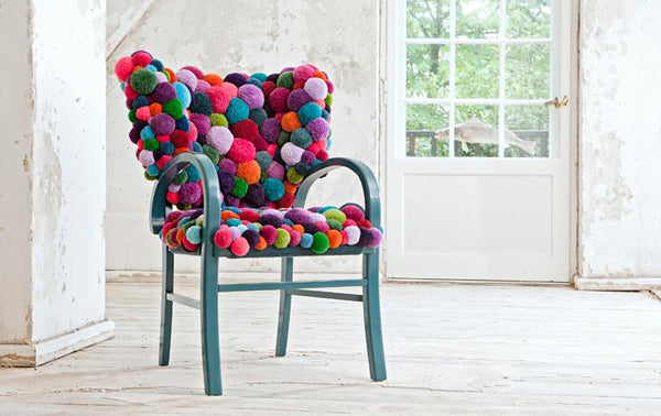 Metal teal chair covered in a bobbled multi coloured back an seat pad