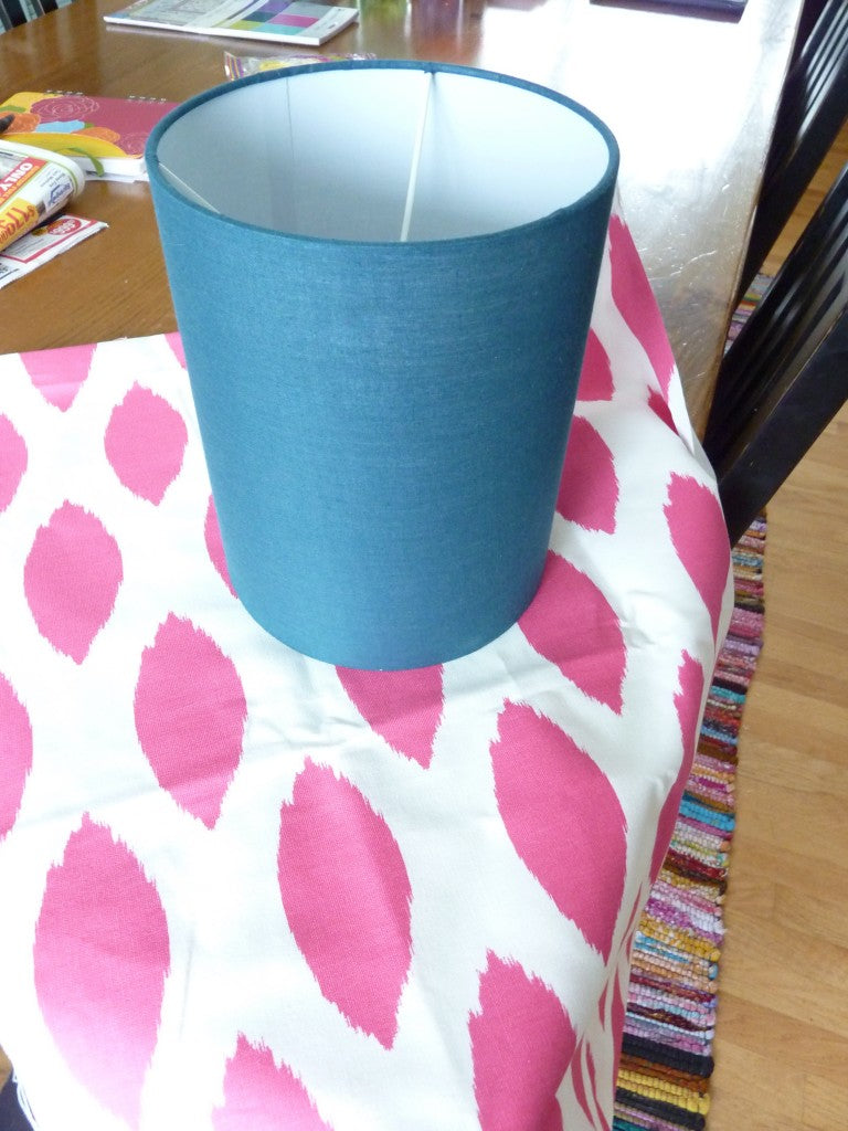 Dark blue lampshade placed on top of a piece of cream and pink fabric