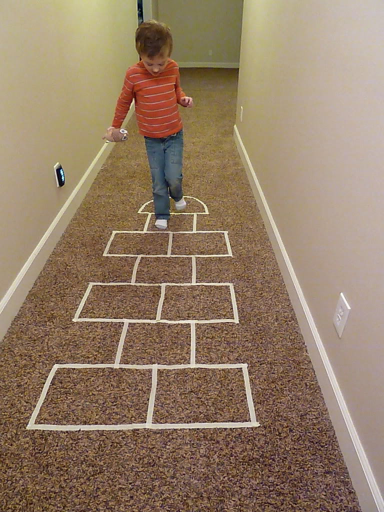 Young boy playing hopscotch using masking tape on a carpet