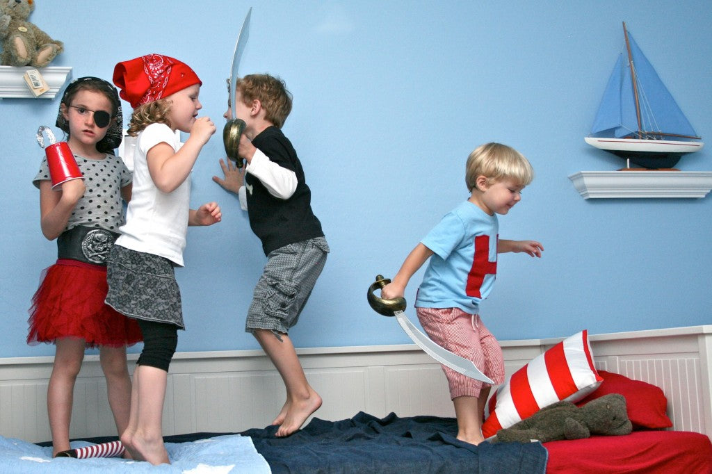 Four children jumping on a bed dressed as pirates