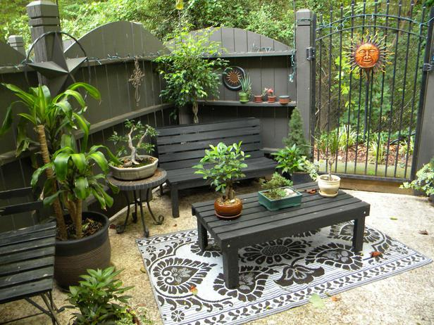 Small patio with wooden garden table, wooden chairs and, fencing all in dark green and grey wood