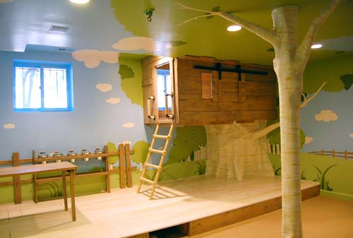 Fun kids bedroom with a tree house style, with raised tree house bed, and a tree painted on the wall and ceiling