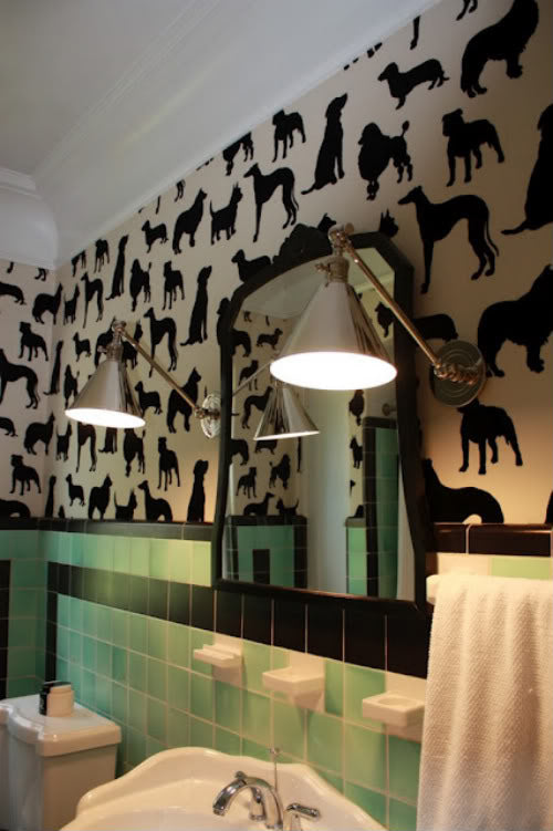 Bathroom with light green and black tiles, then beige wallpaper above the tiles with black dog repeat pattern
