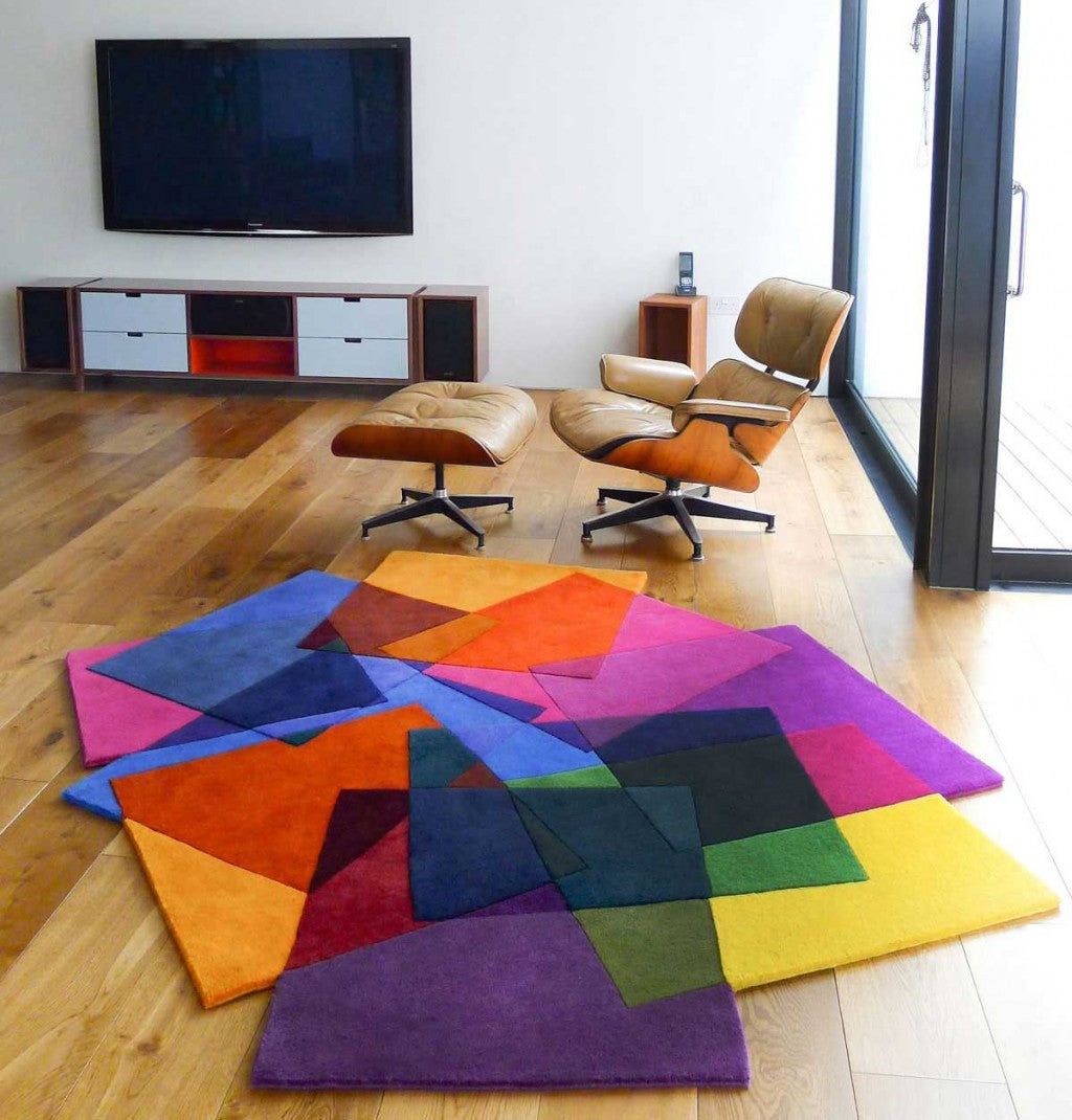 Multi coloured rug with different coloured squares overlapping each other, placed on a lovely wooden floor