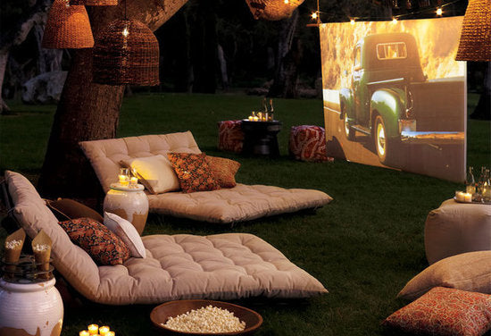 Seatpads and cushions on the grass with bowls of popcorn to watch a film on a projector screen