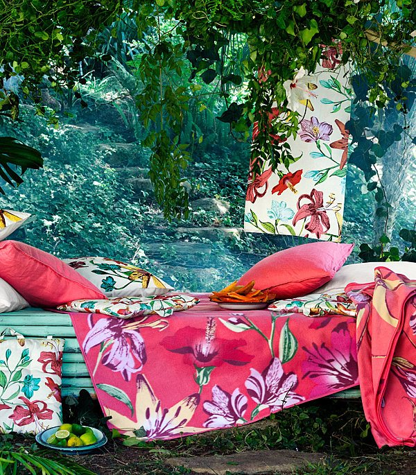 Red floral fabric draped over a mint green bench, next to a rock pool