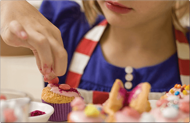 A young girl wearing an apron placing smarties on a cupcake
