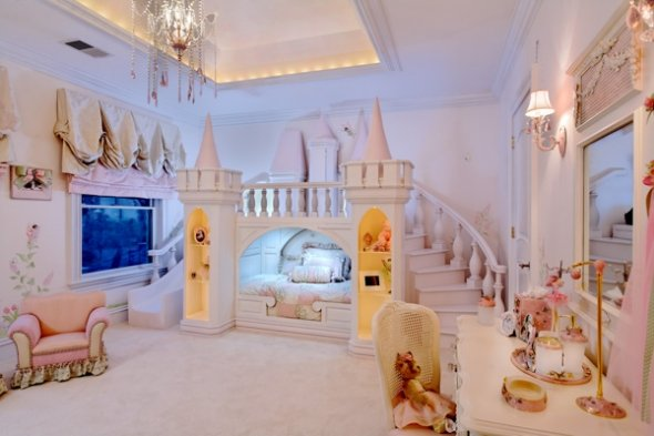 A princess castle themed bedroom with a bed surrounded by turrets and a large slide and staircase