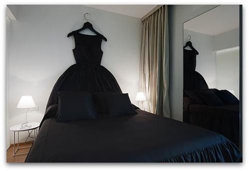A bed with black bedding and then black dress hung above the bed to make a headboard