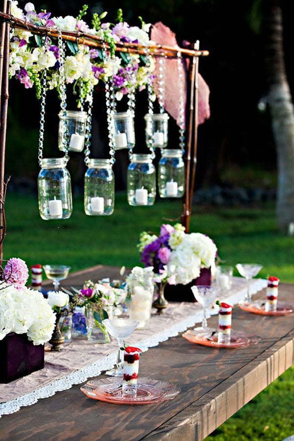 Wooden table in the garden with garden party dessert place settings and glass bottles and jars hanging from bamboo frame