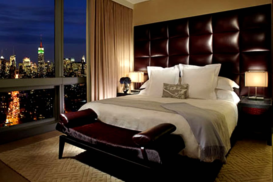 Luxurious bedroom in beige and dark burgundy red, with a night time city view through the window