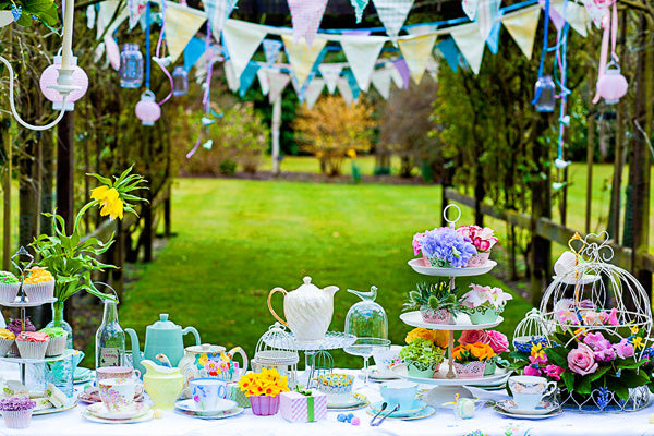 English garden tea party with duck egg, pink, yellow and white teapots, milk jugs, tea cups and matching bunting overhead