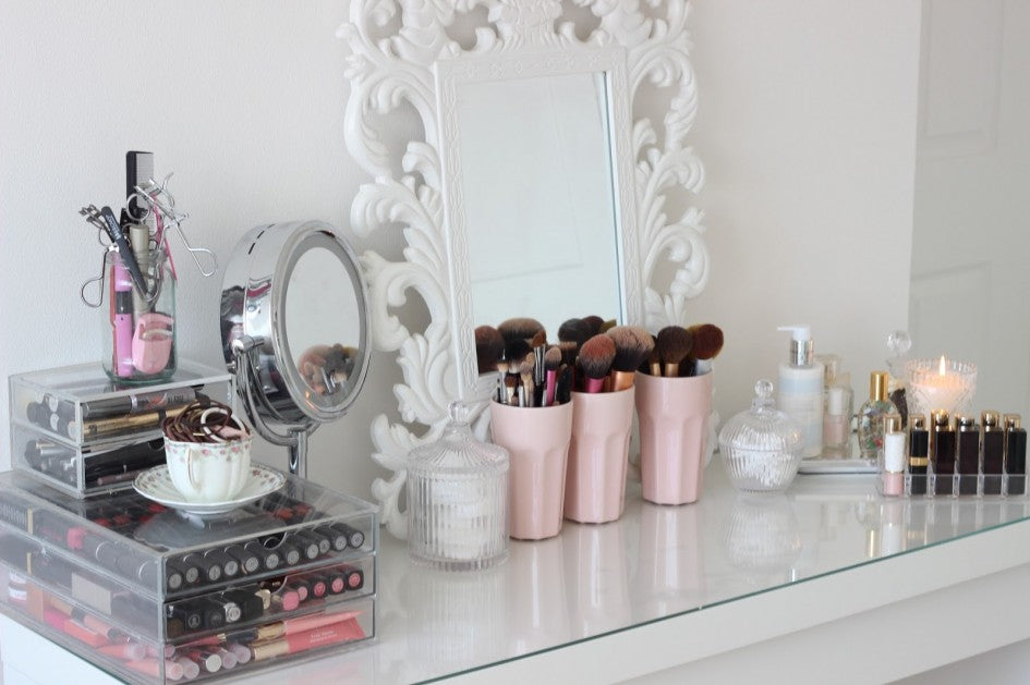 White dressing table with glass top, with white framed mirror and make up accessories
