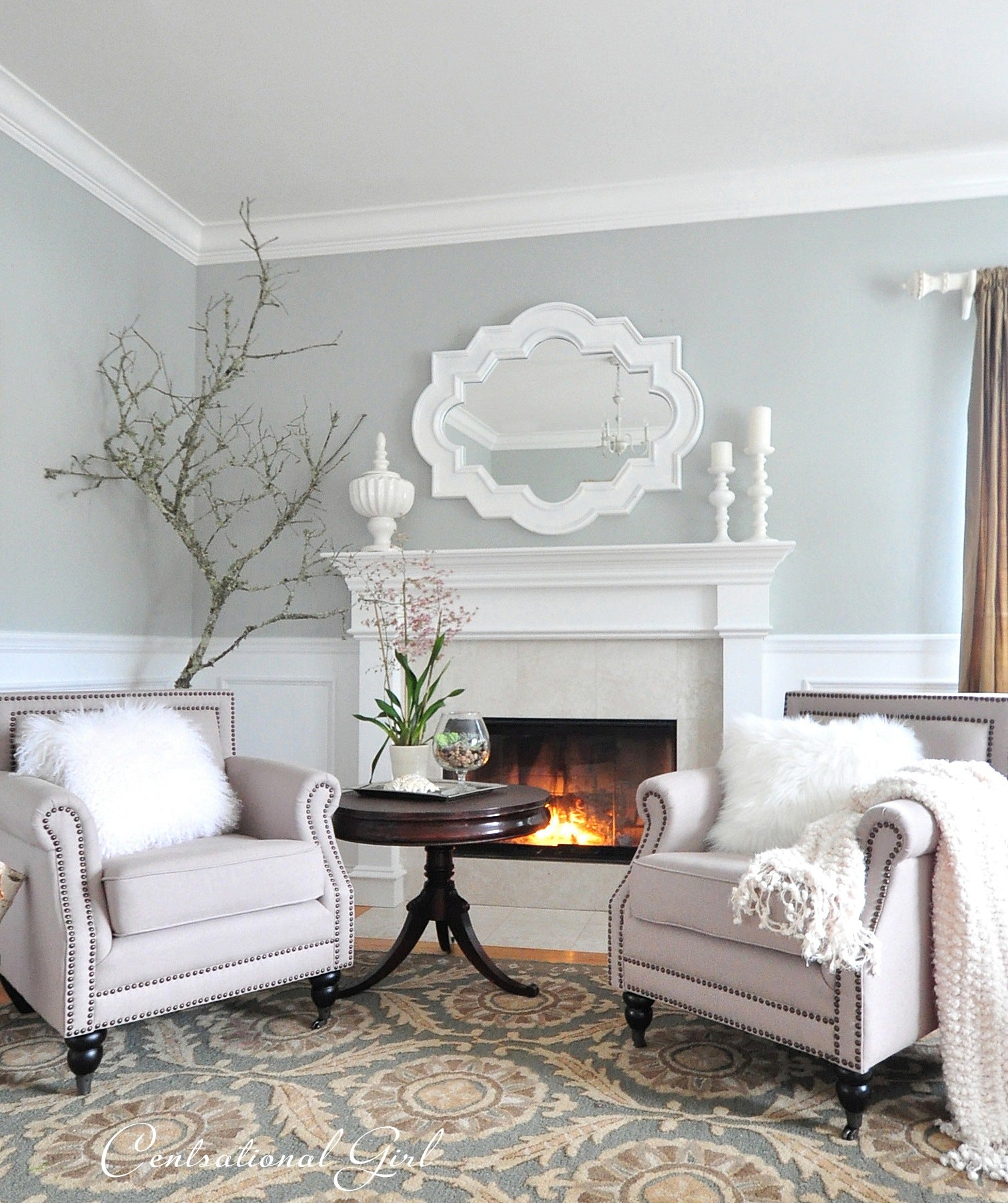 Light blue and white living room, with beige armchairs either side of a white fireplace