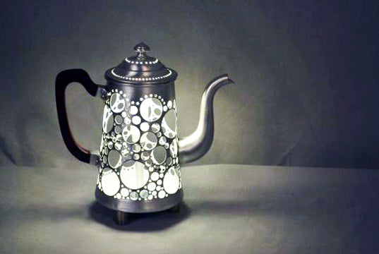 Teapot with light inside it and circle geometric holes all over it, making it look like the surface of the moon