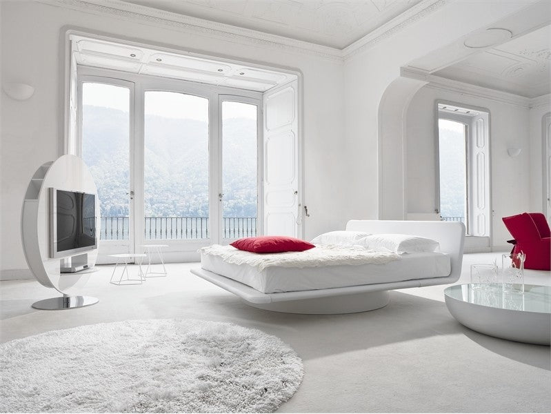 An all white minimalist bedroom with red cushion on the white bed