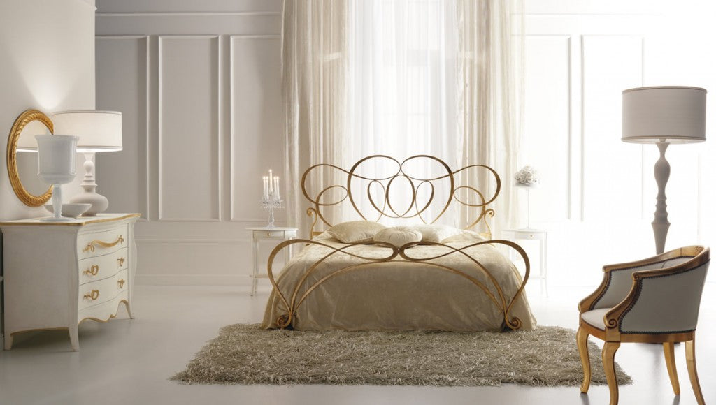 White, cream and gold stylish bedroom with gold coloured metal bed frame with swirling headboard design