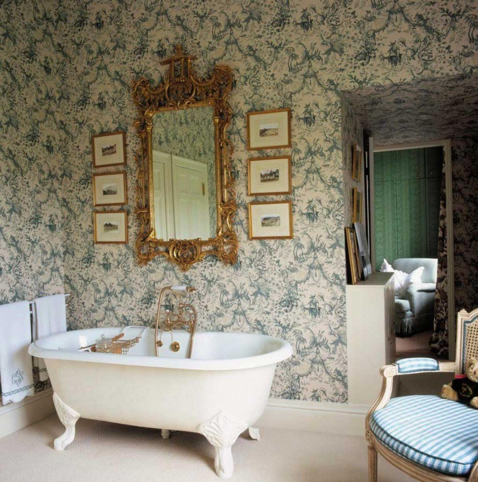 Cream and grey-ish blue patterned wallpaper in a bathroom, with curved white bathtub