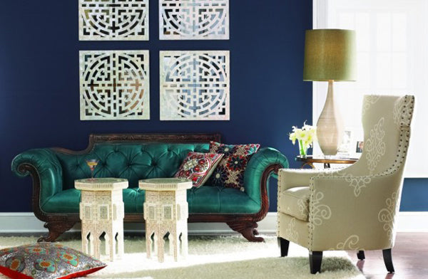 Dark blue living room with Moroccan inspired tables, cushions, green sofa and beige armchair