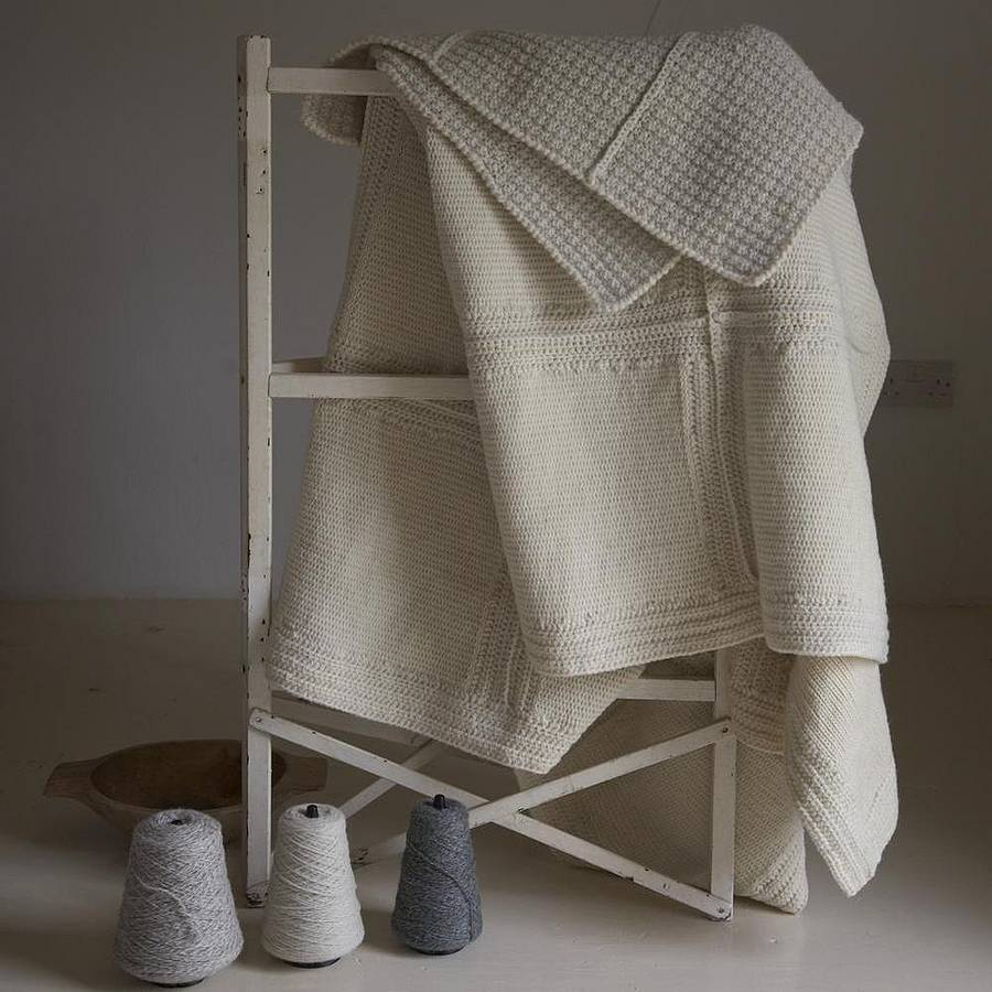 Wooden cream clothes airer, with a cream throw draped over it