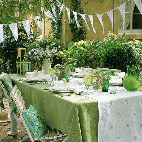 Green and white graden table setting with gree glasses and jugs and white bunting overhead